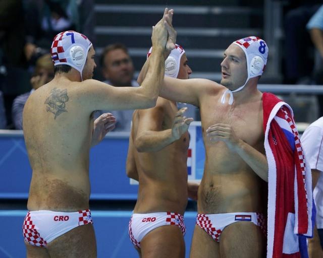 Ватерполист Петар Муслим (слева) празднует победу с товарищами по команде после матча против испанцев. Татуировка на спине