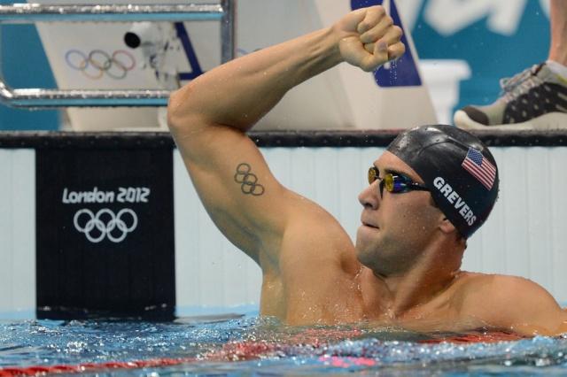 Американский пловец Мэтт Греверс радуется победе в финальном заплыве на 100 метров на спине. Имеет татуировку на внутренней стороне руки в виде Олимпийских колец