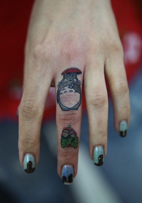 фото татуировки из мультфильма Мой сосед тоторо на женском среднем пальце